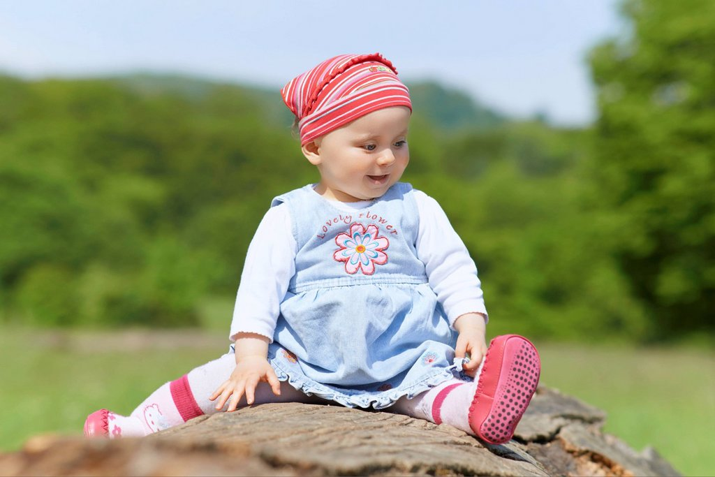 Stock Photo: 1841-123096 Happy female baby sitting on tree stump