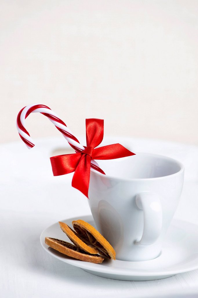 Stock Photo: 1841-128639 Cup decorated with candy cane, red ribbon and dried slices of orange