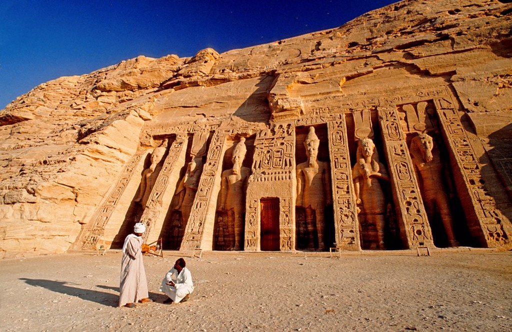Two people in front of Egyptian temple, Nefertaris Temple Of Hathor, Abu Simbel, Egypt : Stock Photo
