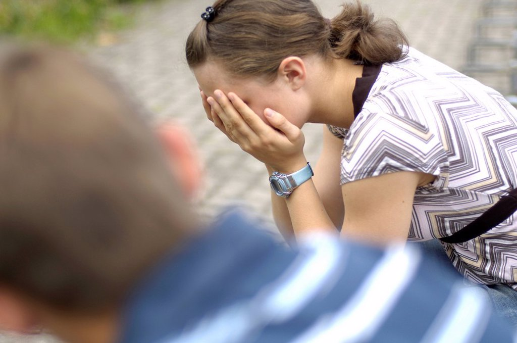 Stock Photo: 1841-14458 Side profile of teenage girl sobbing with her friend sitting beside her