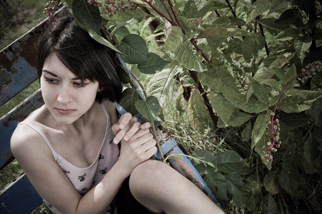 Stock Photo: 1841-15431 Junge Frau sitzt im Park