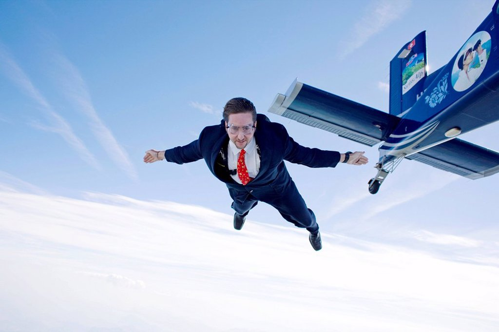 Businessman jumping out of propeller plane, Switzerland : Stock Photo