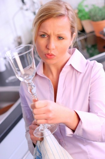 Young woman checking the cleanliness of a goblet, elevated view : Stock Photo