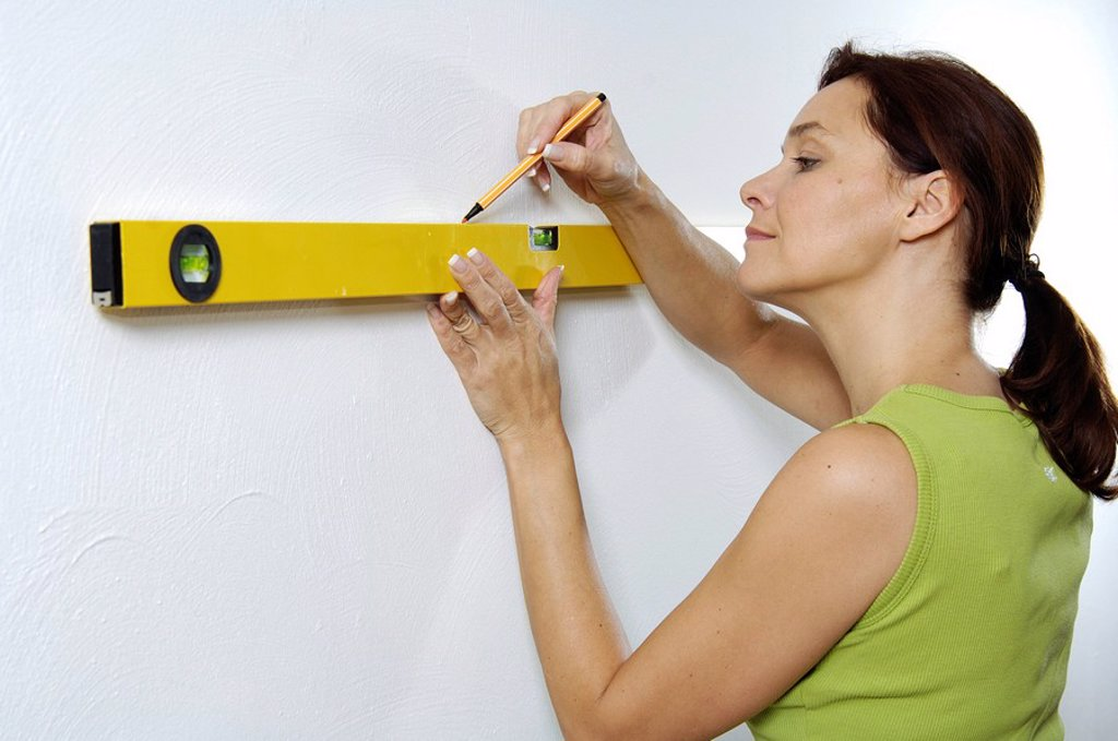 Close_up of woman using spirit level to mark wall : Stock Photo