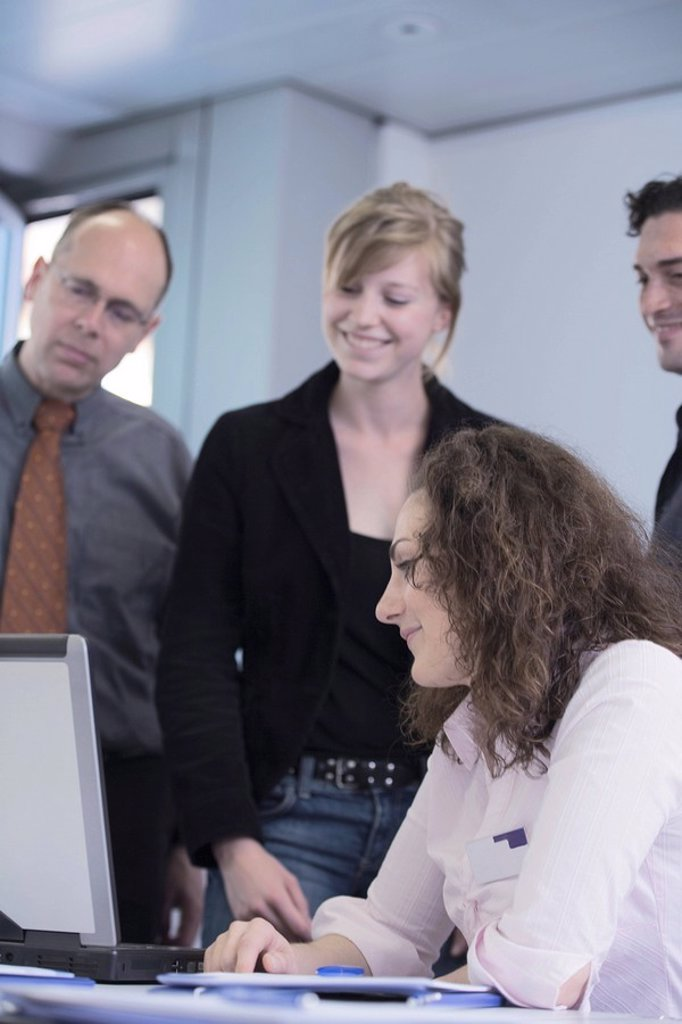 Businesswomen and businessmen looking at laptop and smiling : Stock Photo