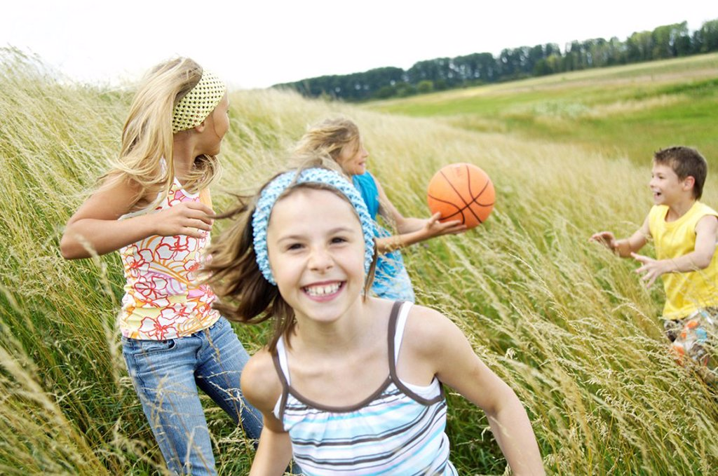 Four children playing in field : Stock Photo
