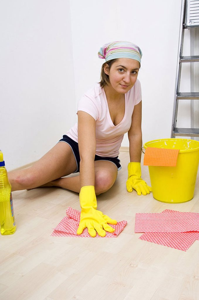 Portrait of young woman cleaning floor : Stock Photo
