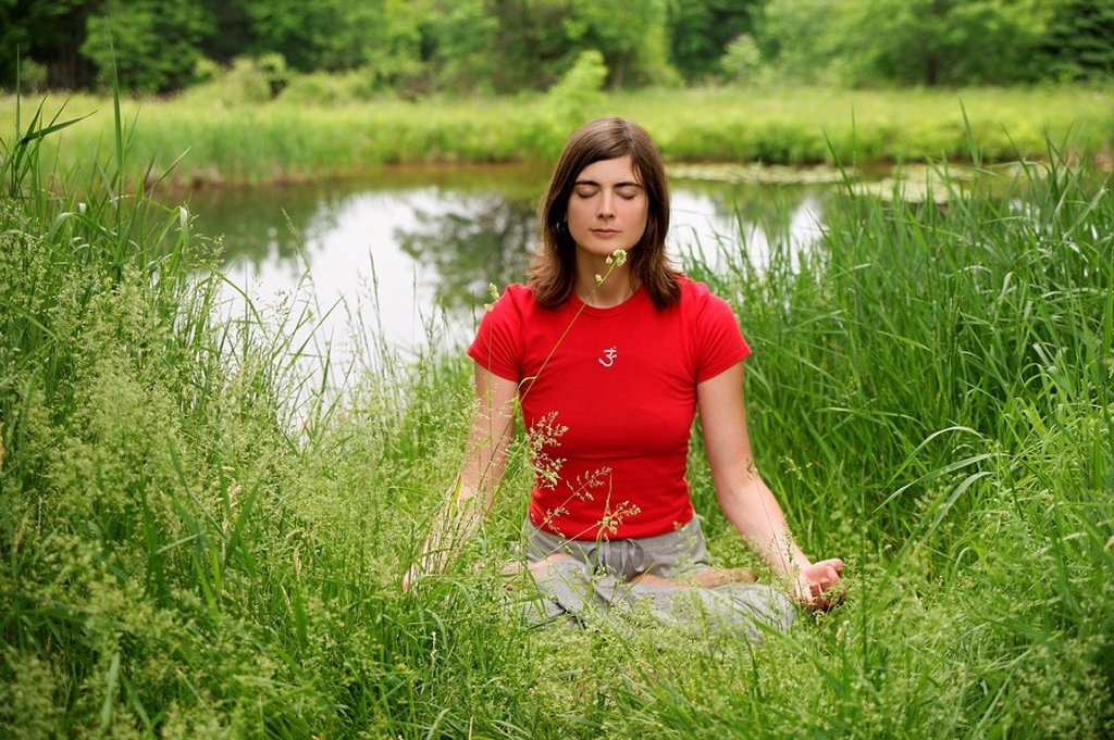Woman meditating by a pond, front view : Stock Photo