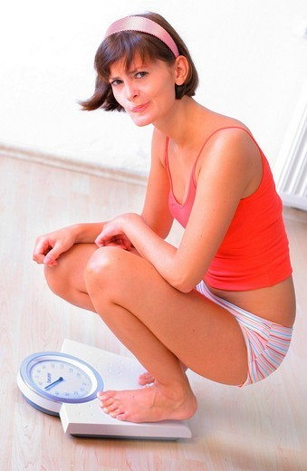 Woman squatting on scale : Stock Photo