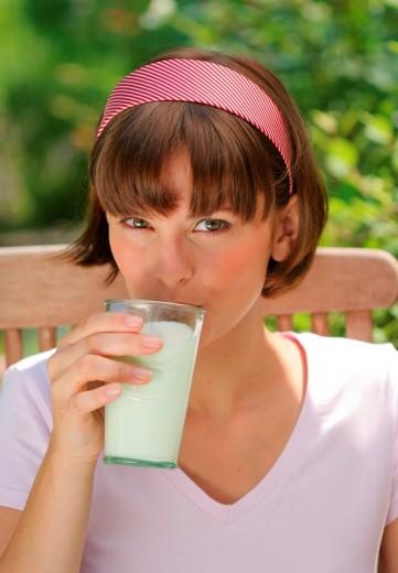 Woman drinking a glass of milk, portrait : Stock Photo