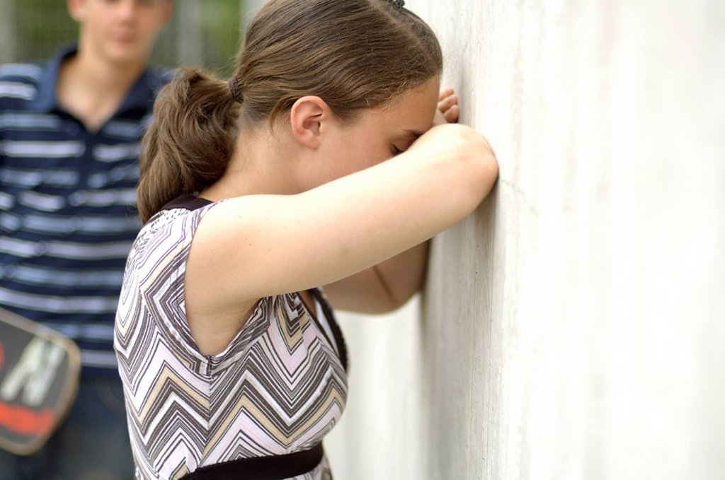 Side profile of teenage girl sobbing against wall with her friend in background : Stock Photo
