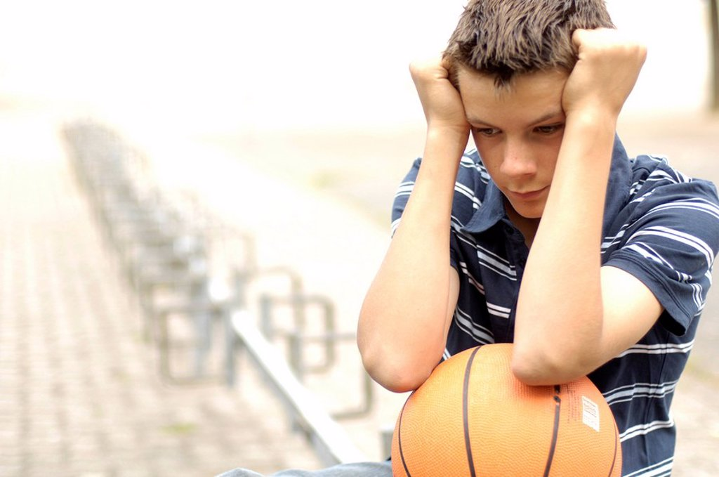 Stock Photo: 1841-26039 Close_up of teenage boy looking serious and holding basketball