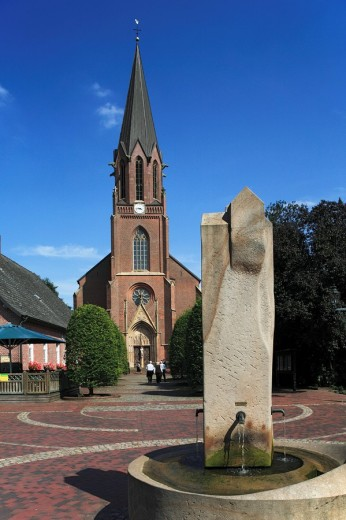 Saint Catherine of Siena church in Lindern Oldenburg, water fountain in the foreground, Germany : Stock Photo