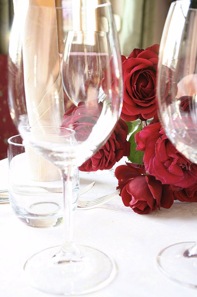 Stem glasses and bunch of roses on table : Stock Photo