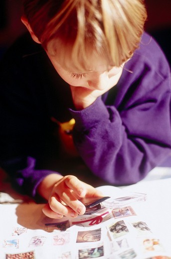 Close_up of boy collecting stamps : Stock Photo