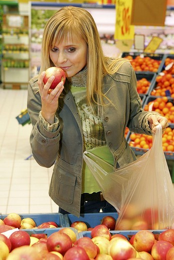 Young woman smelling an apple in supermarket : Stock Photo
