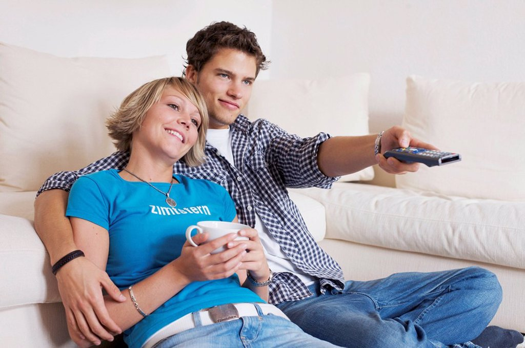 Teenager couple sitting in front of couch and watching television, horizontal format : Stock Photo