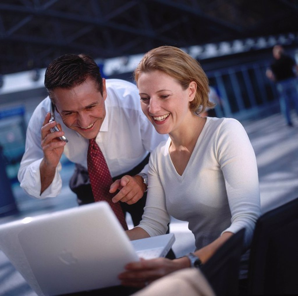 Two businesspeople with laptop and moblie phone : Stock Photo
