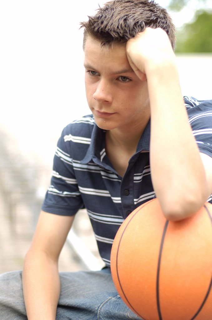 Stock Photo: 1841-31604 Close_up of teenage boy looking serious and holding basketball