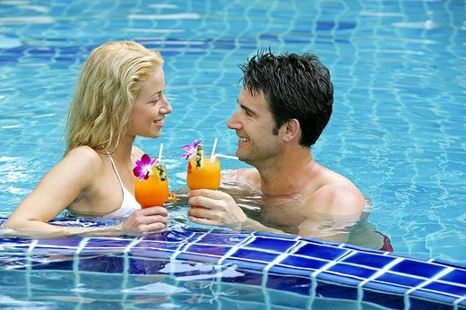 Side profile of young couple holding glasses of cocktail in swimming pool, Thailand : Stock Photo
