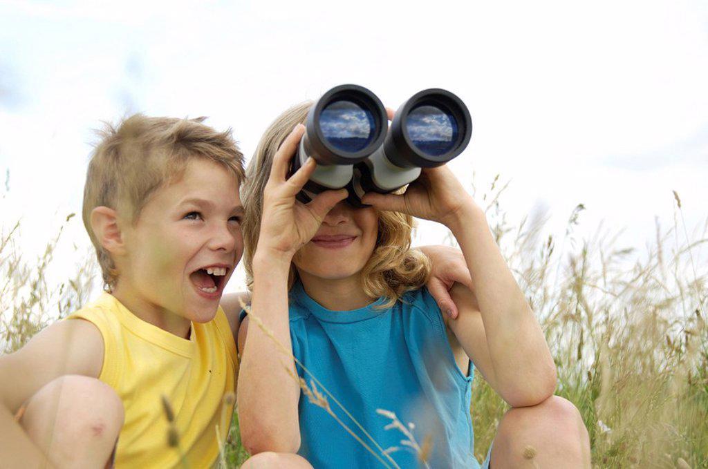 Boy looking through binoculars in field with his friend sitting beside him : Stock Photo