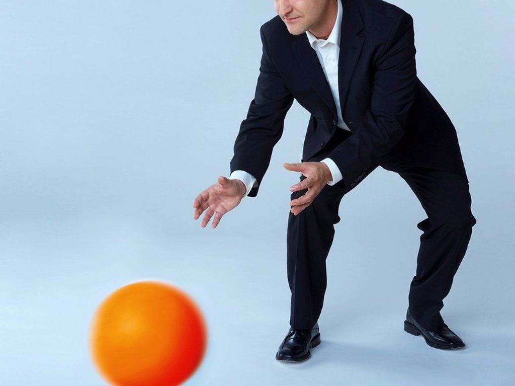 Businessman catching ball : Stock Photo