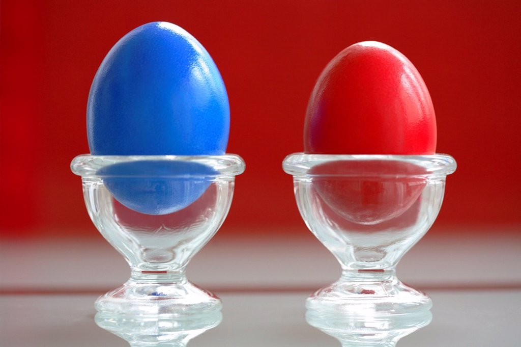 Close_up of two Easter eggs in egg holders : Stock Photo