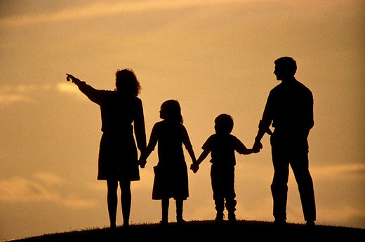 Stock Photo: 1841-37332 Silhouette of parents with two children at dusk