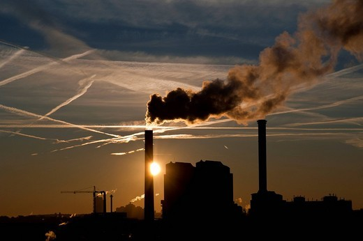 Silhouette of factory emitting smoke at dusk : Stock Photo