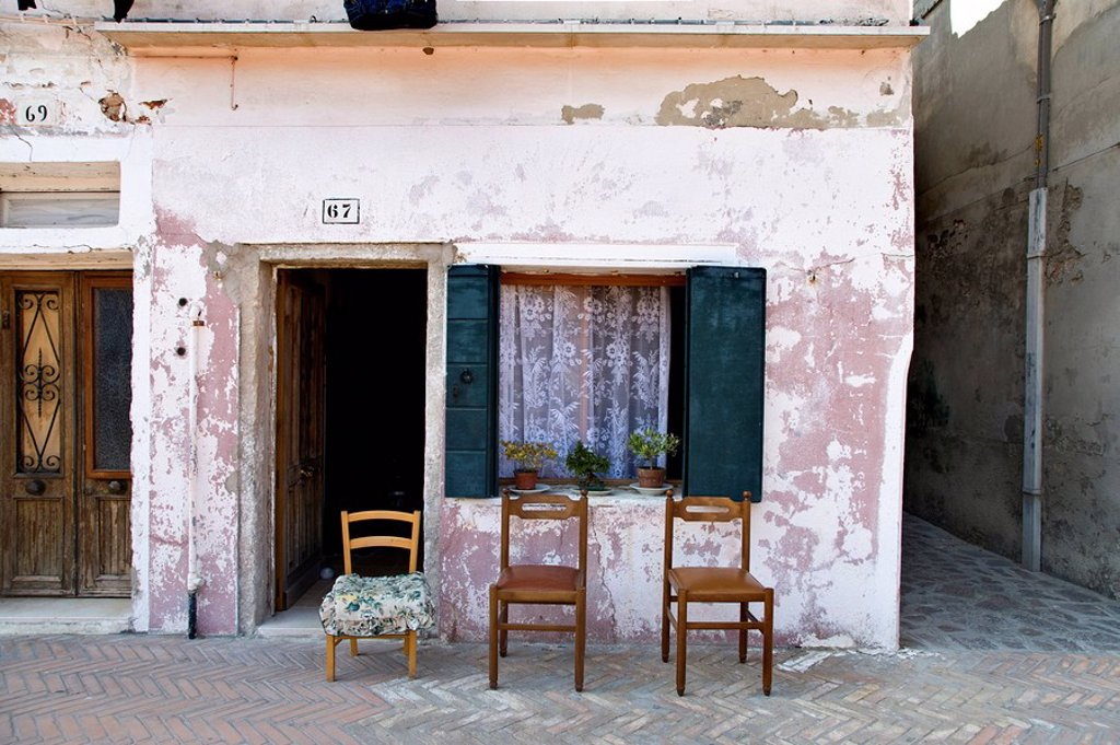 Three chairs in front of an old house, Burano, Italy : Stock Photo