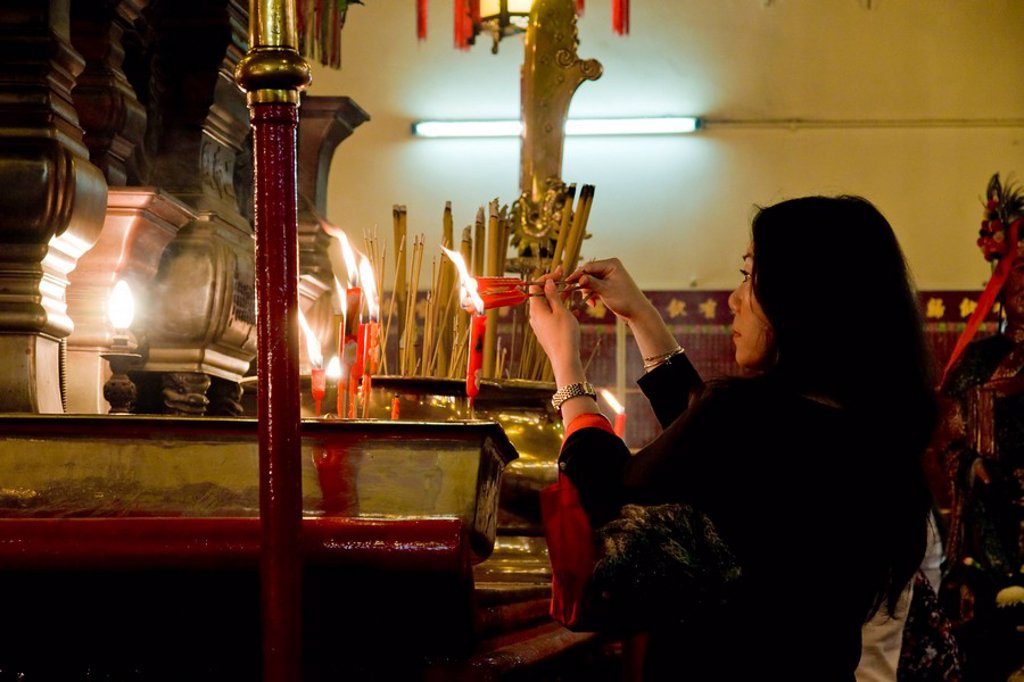 Stock Photo: 1841-37922 Woman lighting candle in Buddhist temple