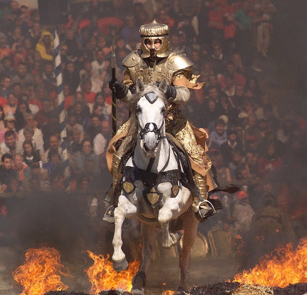 Knight in armour suit riding horse through fire, Bavaria, Germany : Stock Photo