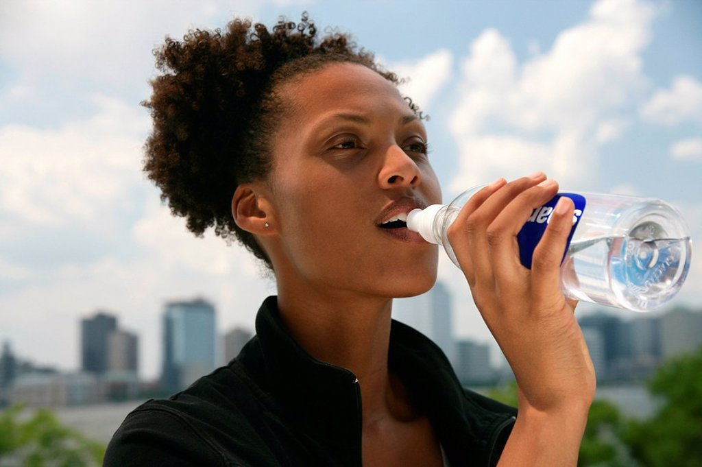 Stock Photo: 1841-40621 Woman drinking from a water bottle, New York City skyline in the background, portrait