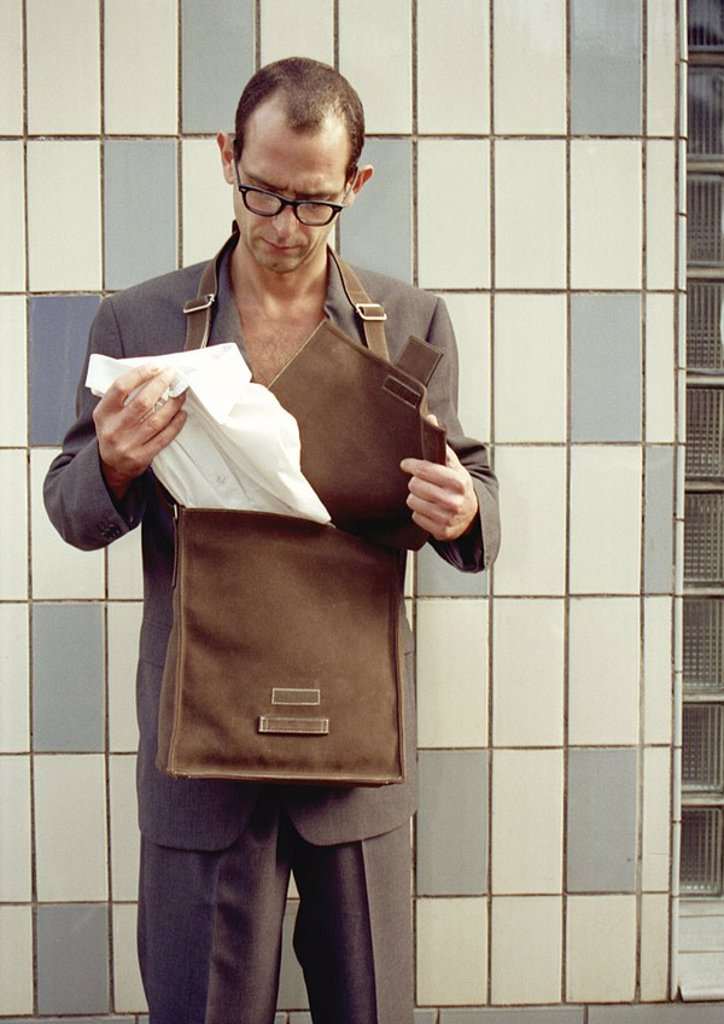 Stock Photo: 1841-40691 Man 30-35 years 30-40 years 35-40 years Suit elegant Pocket Cape pocket Leather pocket open Curiosity open stop remove white shirt Shirt Surprise People Eyeglasses Wall Tiles Tile wall Glass bricks style Adults