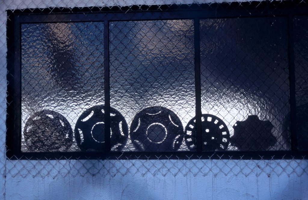 Stock Photo: 1841-40791 Silhouette of handcraft materials behind chain_link fence