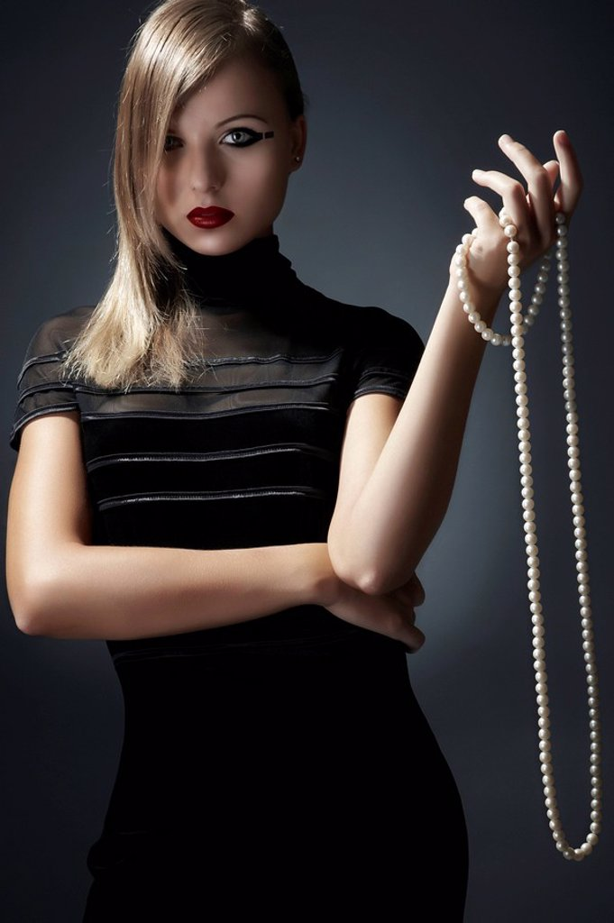 Stock Photo: 1841-41214 Young woman holding pearl necklace in her hand