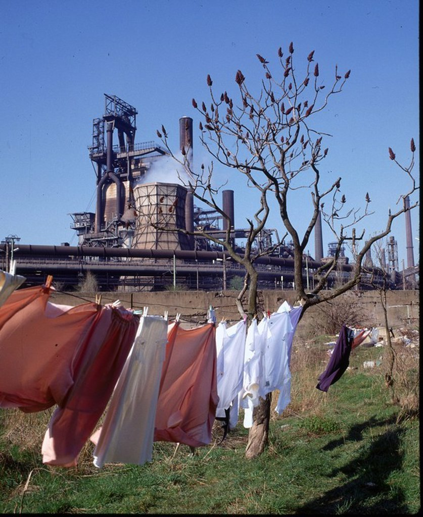 Clothes drying on clothesline with smelting plant in background, Germany : Stock Photo