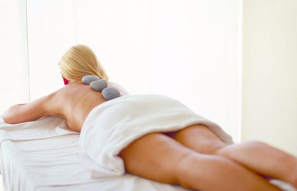 Rear view of naked young woman receiving hot stone treatment : Stock Photo