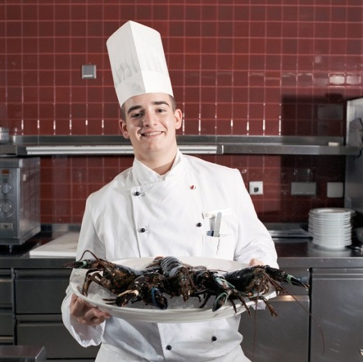 Cook holding plate with lobsters : Stock Photo