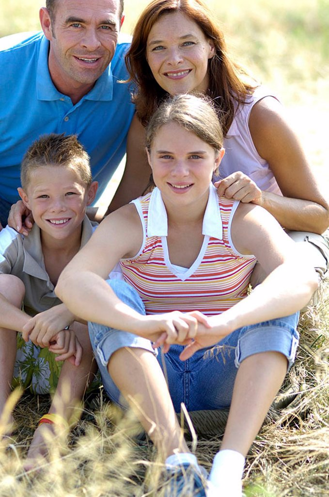 Portrait of family smiling in field : Stock Photo