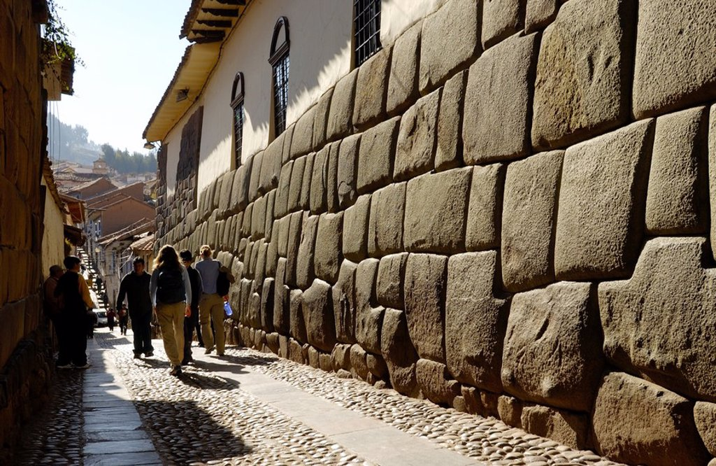 Tourists walking near stone wall, Inca Ruins, Machu Picchu, Cusco Region, Peru : Stock Photo