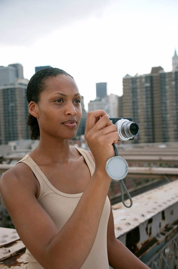 Woman standing on the Brooklyn Bridge and holding a digital camera, skyline of New York in the background, USA : Stock Photo