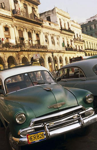 Taxis parked in row in front of buildings, Havana, Cuba : Stock Photo