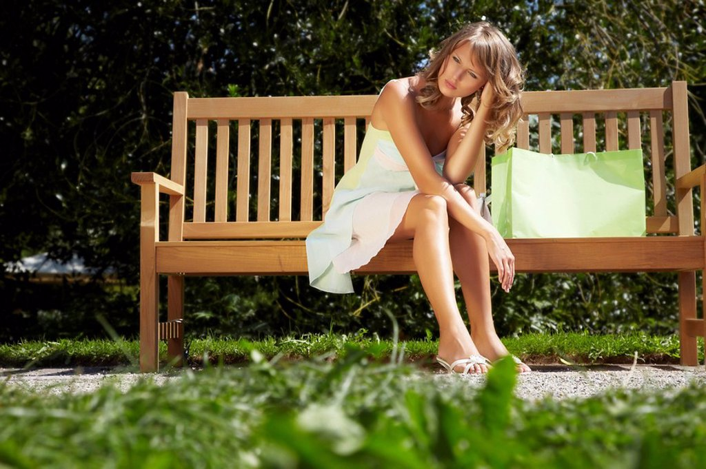 Young woman resting on a park bench : Stock Photo