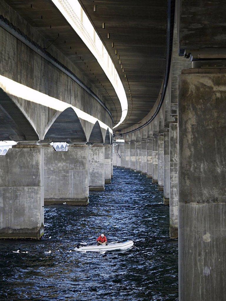 Person on boat under bridge, Denmark : Stock Photo