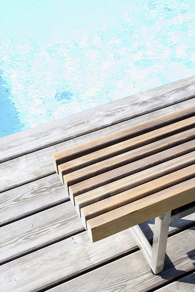 High angle view of empty bench at edge of swimming pool : Stock Photo