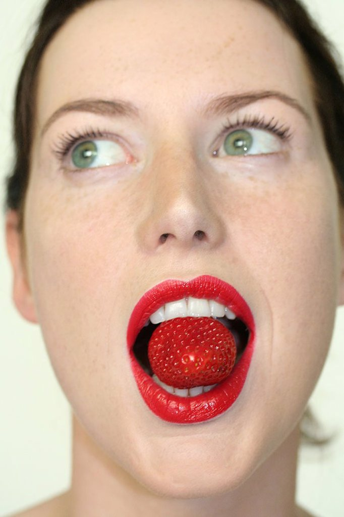 Young woman holding strawberry in mouth : Stock Photo