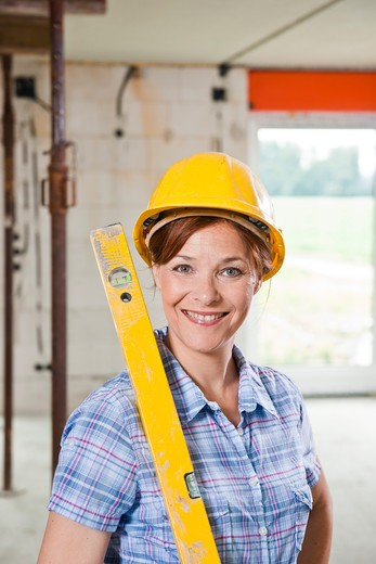 Woman with level and helmet : Stock Photo