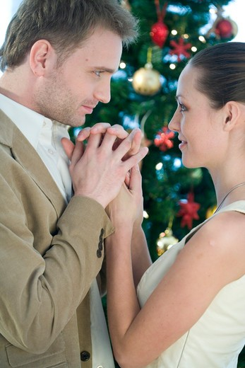 couple holding their hands next to christmas tree : Stock Photo