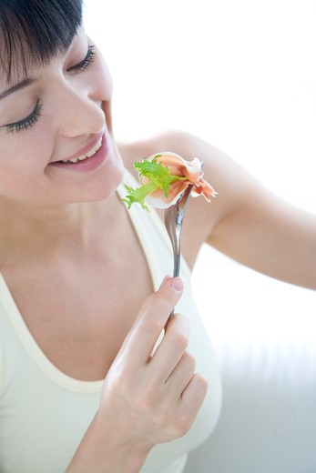woman eating lettuce with slice of ham : Stock Photo
